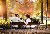 Rear view of happy African American family communicating while relaxing on a park bench in autumn day.