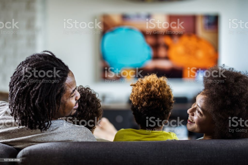 Back view of happy black parents talking while watching TV with their kids at home. stock photo