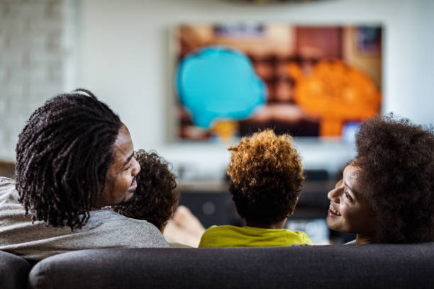 back view of happy black parents talking while watching tv with their kids at home. - family watching tv stock photos and pictures