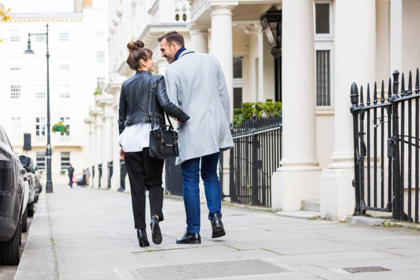 Back view of happy elegant couple walking in the city street stock photo