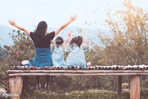 Back view of happy family mother and two child girls sitting and looking at nature together in vintage color tone