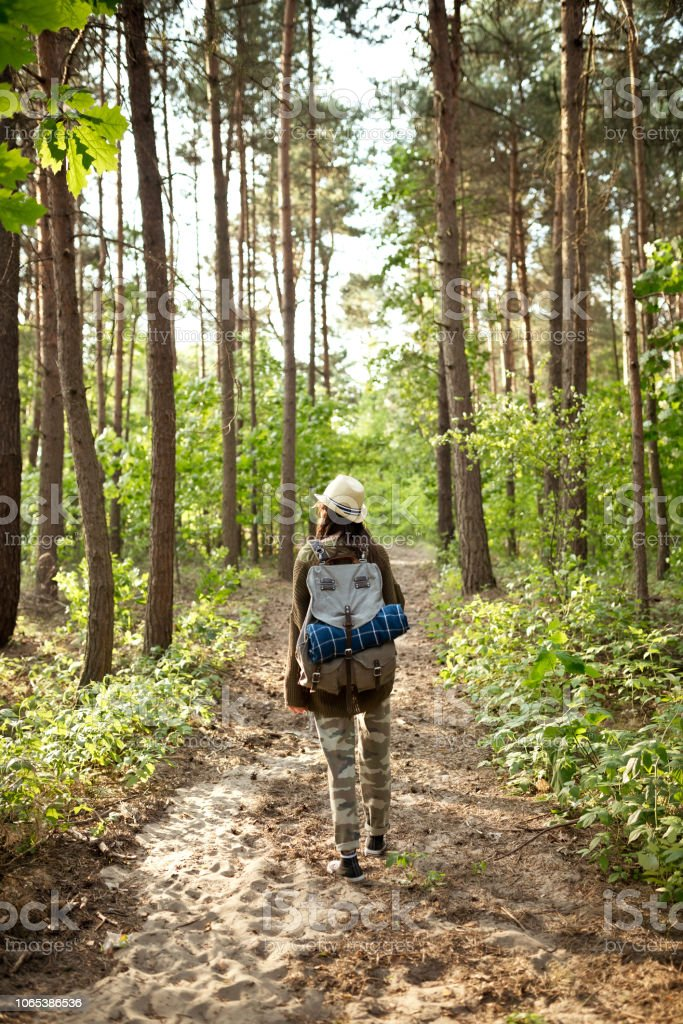 Back view of hipster girl hiking in the woodland Outdoor shot of young woman walking in the forest, holding backpacks. Adolescence Stock Photo