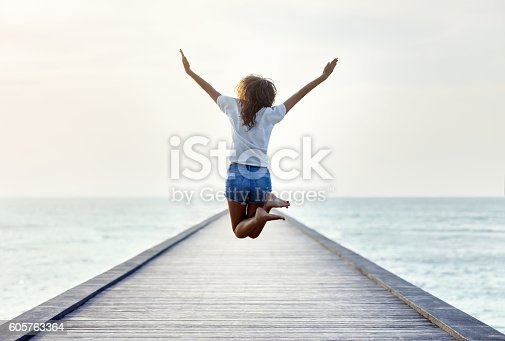 istock Back view of jumping girl on the pier 605763364