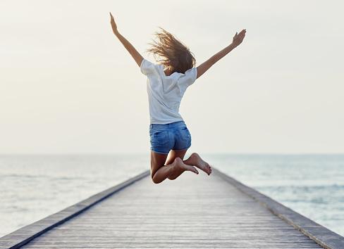 Back View Of Jumping Girl On The Pier Stockfoto und mehr Bilder von Aktivitäten und Sport