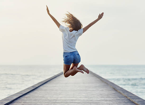 Back view of jumping girl on the pier - foto de stock