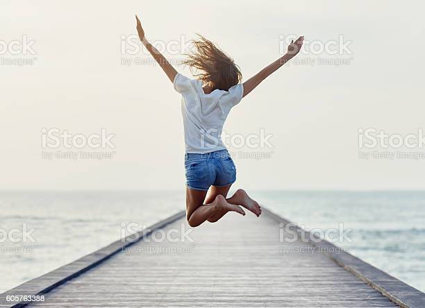 Back view of jumping girl on the pier. Freedom concept