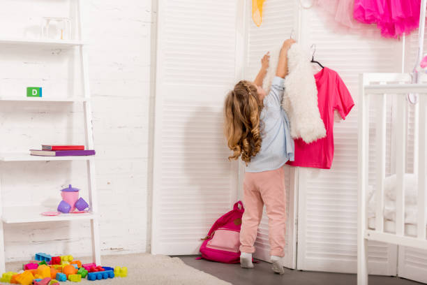 rückansicht des kind unter kleiderbügel mit kleidung aus paravent im kinderzimmer - raumteiler weiß stock-fotos und bilder