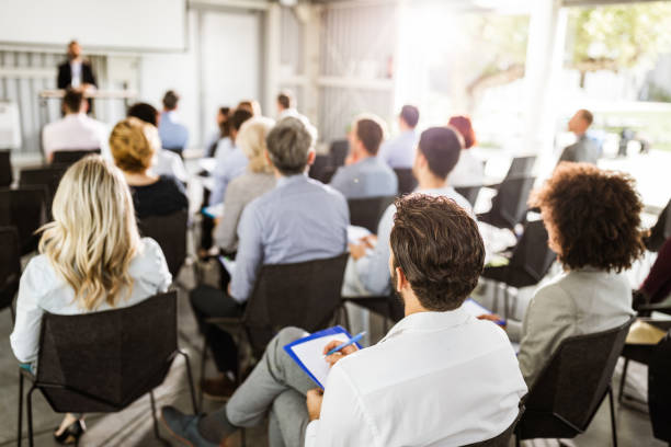 Back view of large group of entrepreneurs on a seminar. stock photo