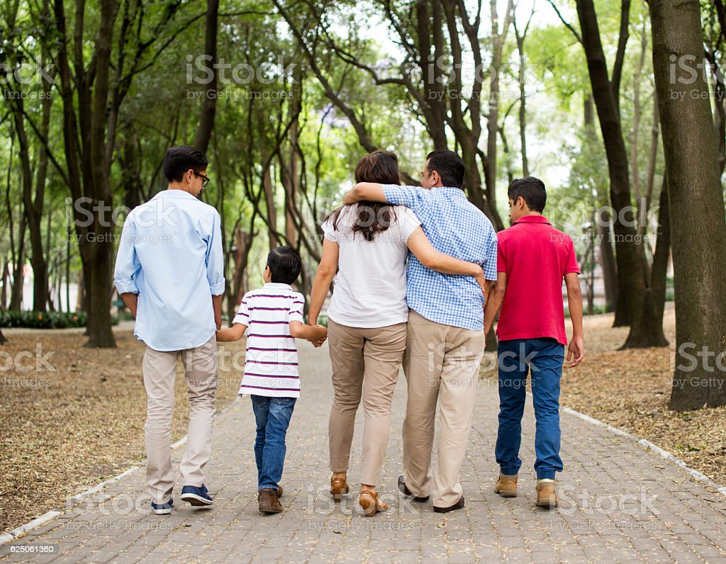 Back view of latin family walking together outdoors stock photo