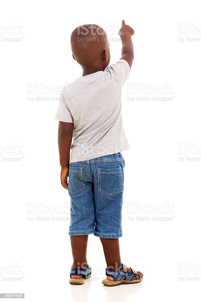 back view of little african boy pointing stock photo