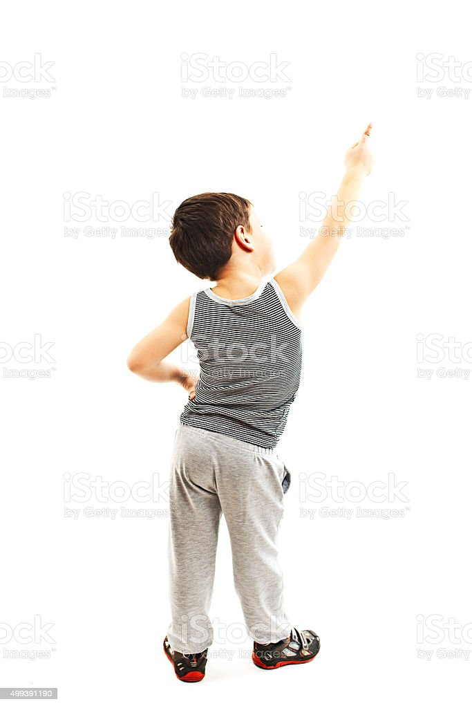 Back view of little boy points at wall. Rear view stock photo