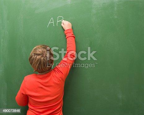 istock Back View Of Little Boy Writing On Blank Blackboard 490073846