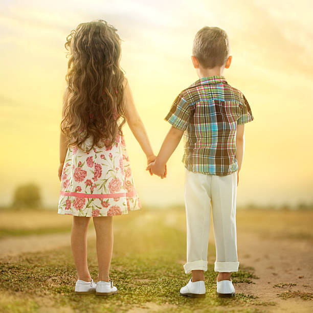 back view of little kids holding hands at sunset - little girls little boys kissing love stock photos and pictures
