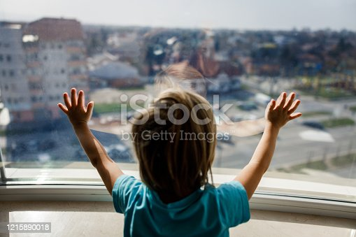 Rear view of a small boy feeling lonely while looking through window in a quarantine.