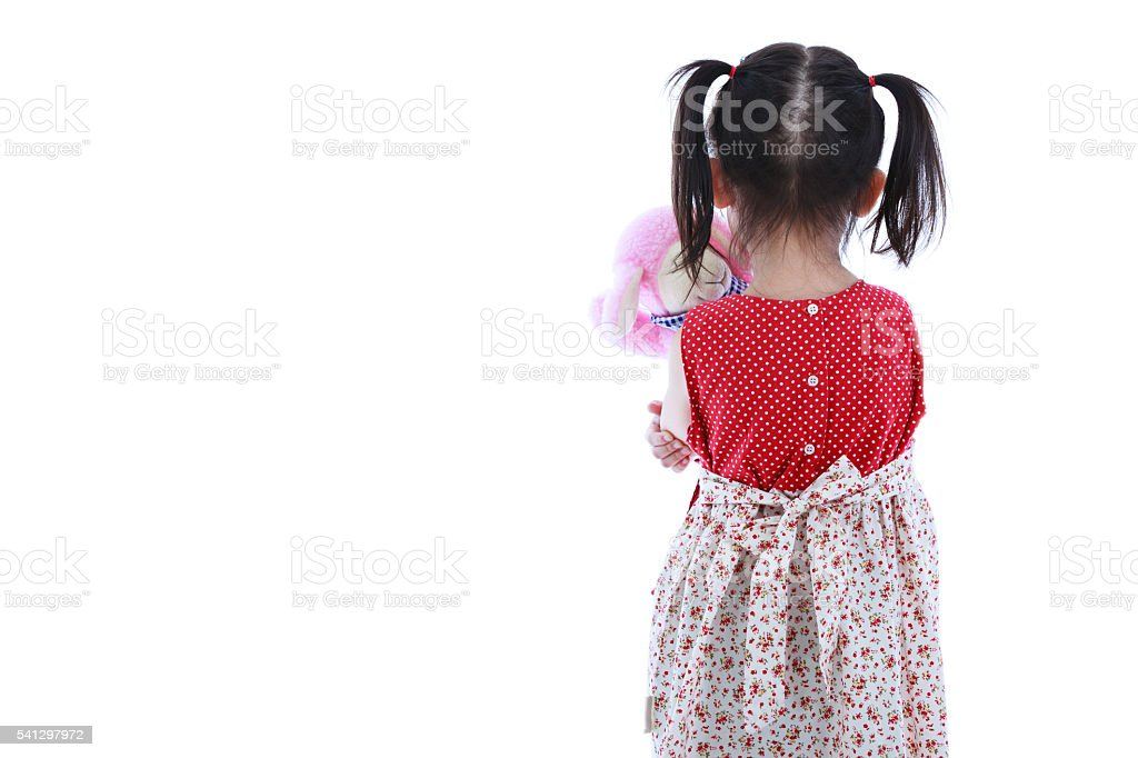 Back view of lonely child with doll sad gesture. Isolated. stock photo