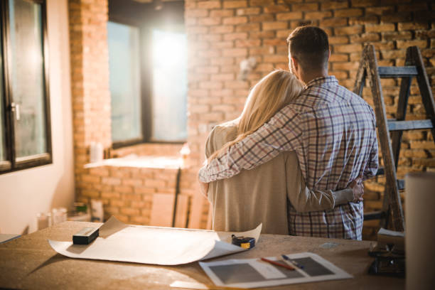 Back view of loving couple standing embraced in their developing apartment. stock photo