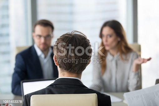 istock Back view of male CEO negotiating with diverse partners 1051453378