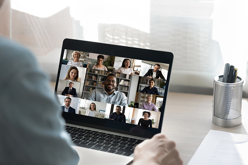 Back view of male employee have online video call on laptop with diverse multiethnic colleagues, man worker involved in webcam conference or virtual event on computer with multiracial businesspeople
