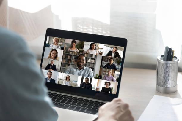 achtermening van mannelijke werknemer heeft webcamconferentie met collega's - medewerkerbetrokkenheid stockfoto's en -beelden