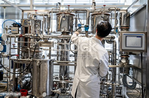 Back view of male student working at the process lab distilling liquids - Education concepts