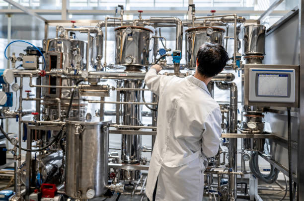 Back view of male student working at the process lab distilling liquids Back view of male student working at the process lab distilling liquids - Education concepts chemical plant stock pictures, royalty-free photos & images