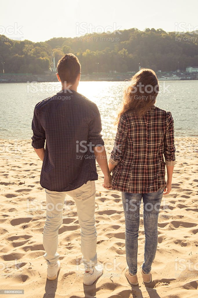 Back view of man and woman in love holding hands stock photo
