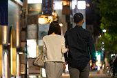 夜の繁華街で手をつないで歩く男女のバックビュー