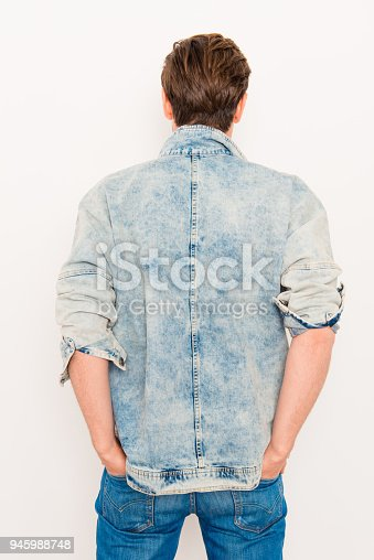 istock Back view of man holding hands in pockets of jeans 945988748