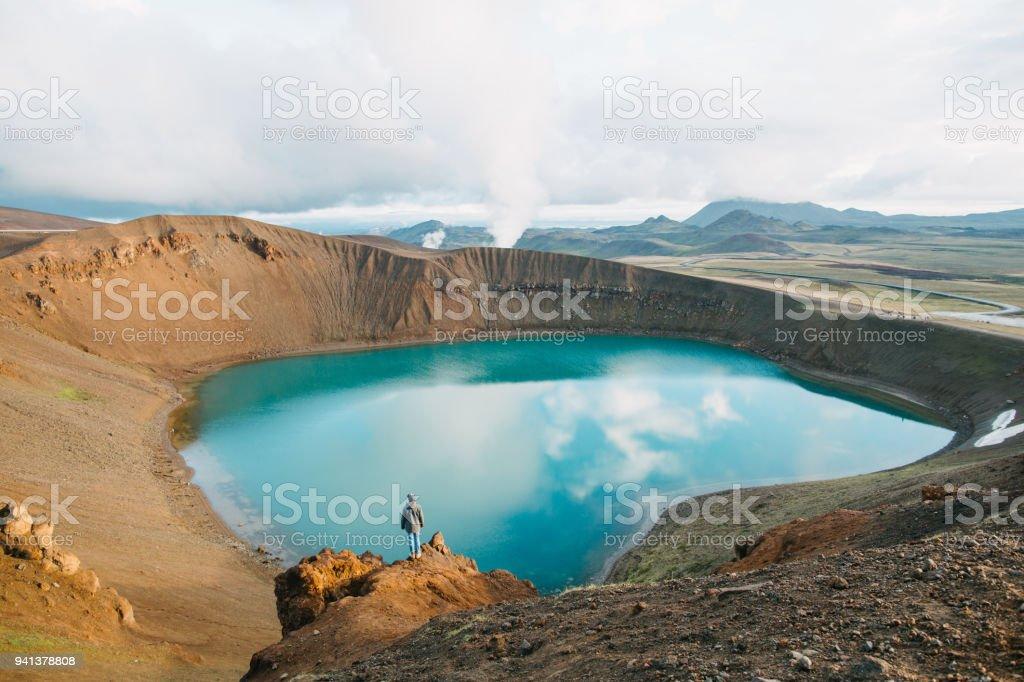 back view of man looking at majestic volcanic lake in iceland, krafla, lake viti stock photo
