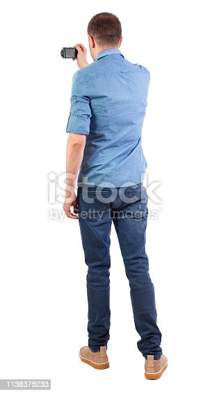 istock Back view of man photographing. tourist with camera. 1138375233