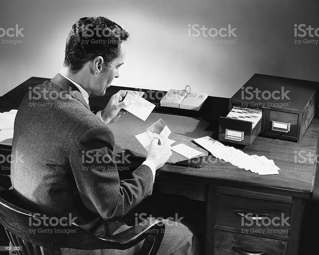 Back view of man sitting and looking at address cards royalty-free stock photo