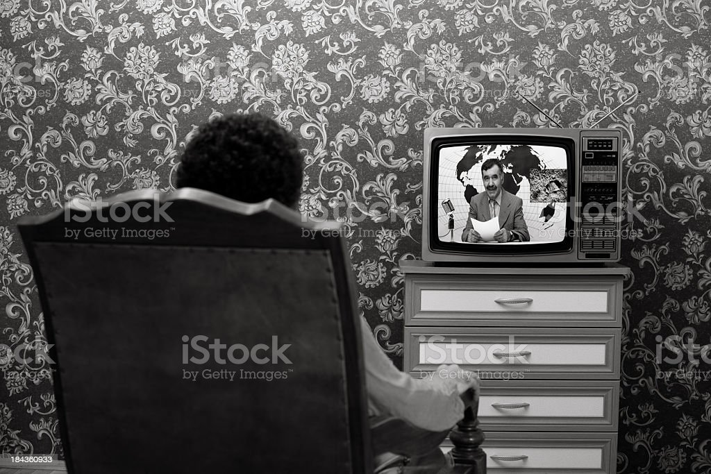 Back View Of Man Sitting And Watching News On Television stock photo