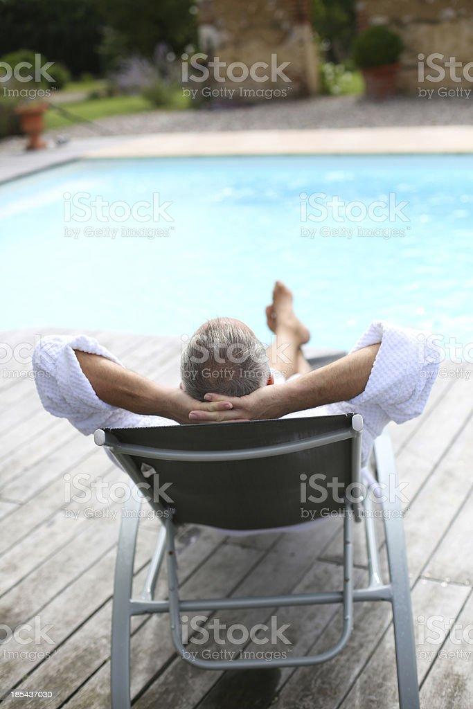 バックの長いの椅子に座って男のプール付近 ストックフォト