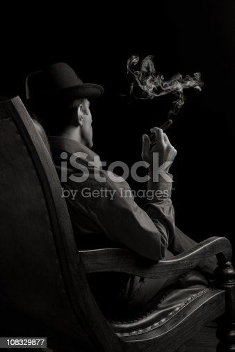istock Back View Of Man Sitting On Armchair And Smoking Cigar 108329877