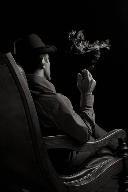 widok z tyłu człowieka siedzi na fotelu i palenie cygar - gangster zdjęcia i obrazy z banku zdjęć