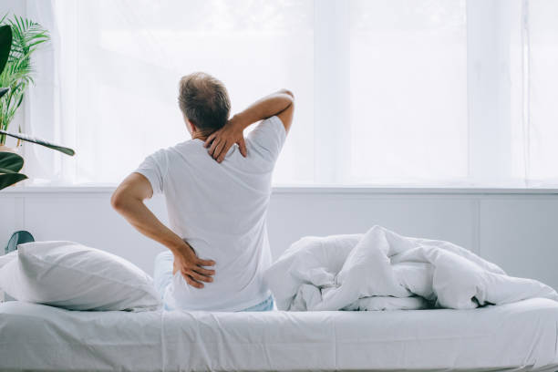 Rückansicht des Menschen am Bett sitzen und leiden unter Rückenschmerzen – Foto