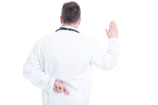 istock Back view of medic or doctor lying about Hippocratic oath 542089808
