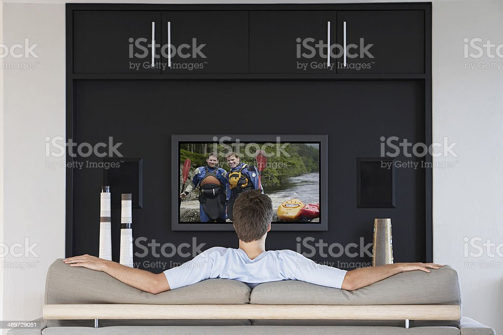 Back view of mid-adult man watching television in living room stock photo