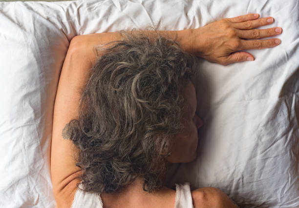 Back view of middle aged woman sleeping on pillow from above High angle close up  view of middle aged woman sleeping face down on pillow with arm overhead (selective focus) face down stock pictures, royalty-free photos & images