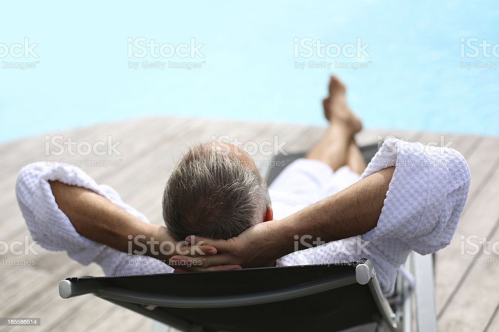 Back view of middle-aged man napping near swimming pool stock photo