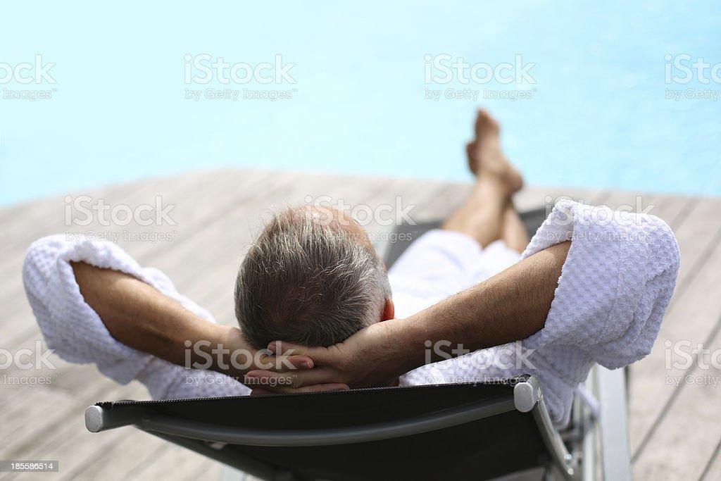 バックの中年男性の昼寝プール近く ストックフォト