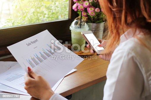 645670208istockphoto Back view of mobile phone with calculator app is used by hands of business woman  in her office. Shallow depth of field 669947792