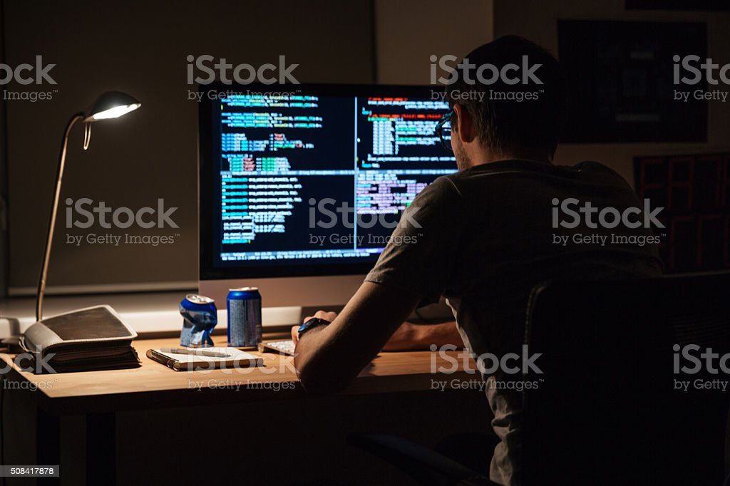 Back view of modern programmer sitting and writing code stock photo