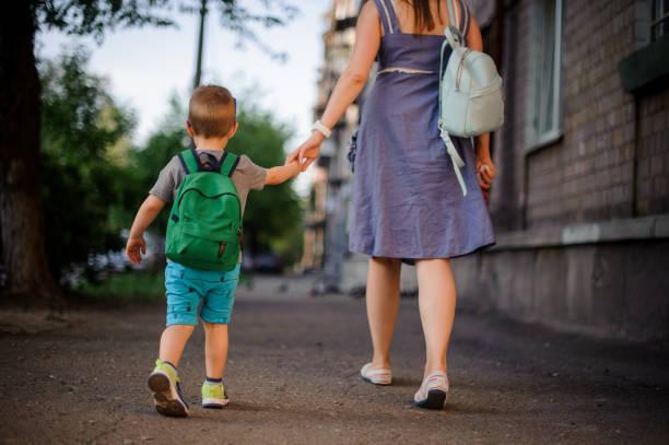 achteraanzicht van moeder gaan met een zoontje met een rugzak - verduisterd gezicht stockfoto's en -beelden