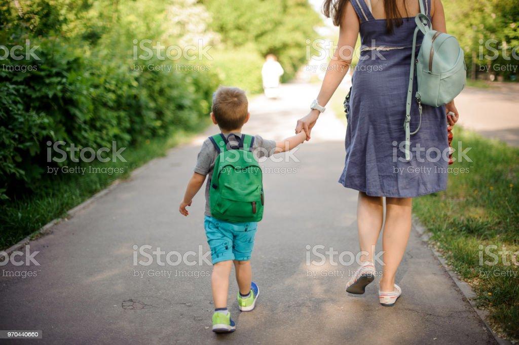 Rückansicht der Mutter auf der Straße mit einem kleinen Sohn mit einem Rucksack auf sonnigen Tag – Foto