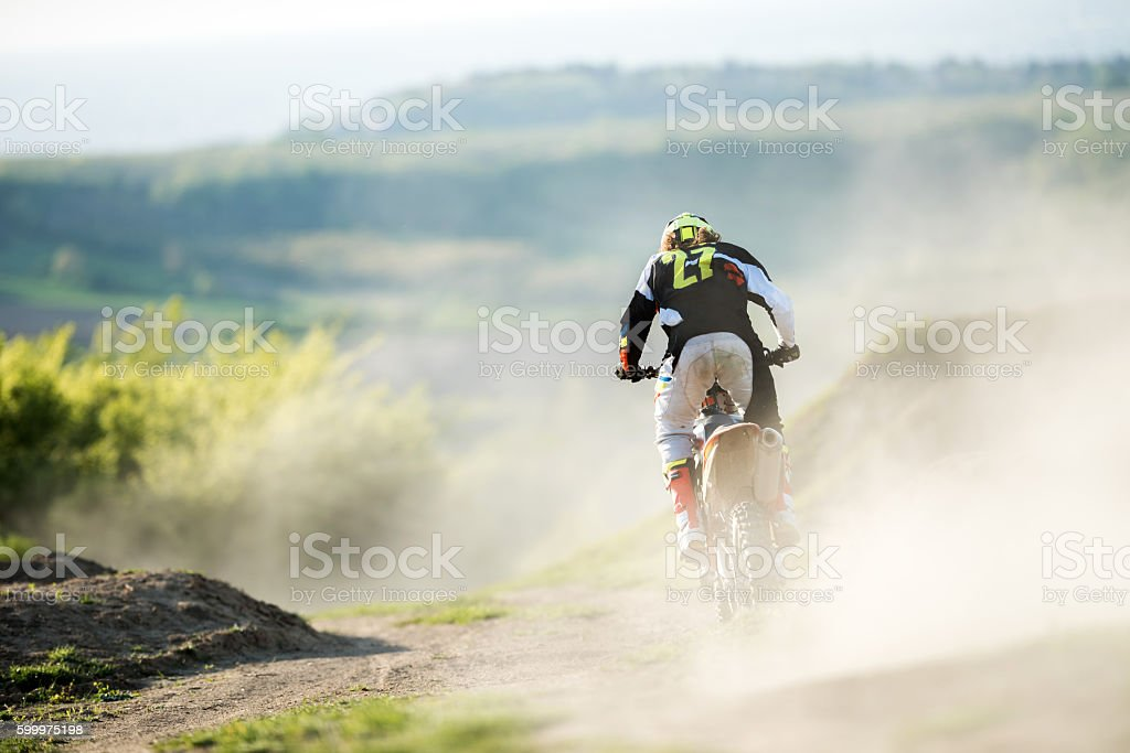 Back view of motocross racer in action on dirt road. stock photo
