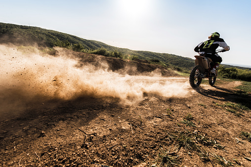 Rear view of dirt bike race riding fast on off-road dirt track.