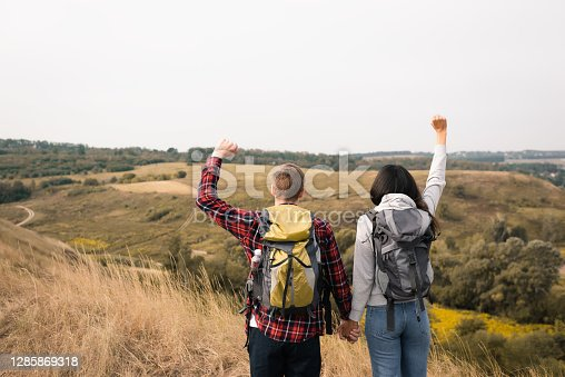 Back view of multiethnic couple of hikers showing yes gesture while holding hands with grassy landscape on blurred background