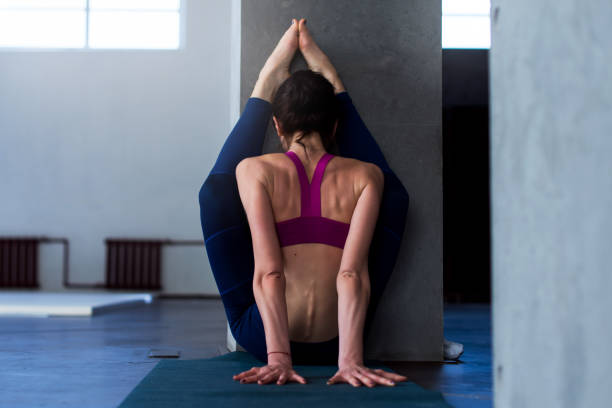 Back view of muscular young woman doing advanced stretching exercise with wall performing variation of upward facing forward bend pose during yoga routine Back view of muscular young woman doing advanced stretching exercise with wall performing variation of upward facing forward bend pose during yoga routine. hamstring stock pictures, royalty-free photos & images