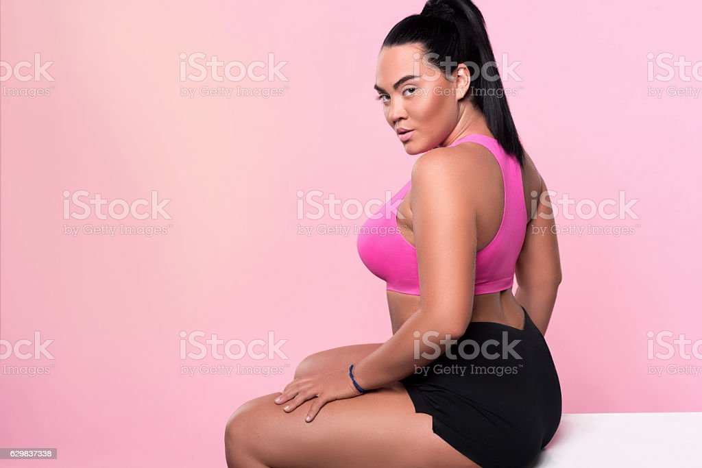 Back view of nice plump sitting woman stock photo